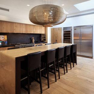Esempio di una cucina a L minimal con ante lisce, ante in legno scuro, paraspruzzi nero, elettrodomestici in acciaio inossidabile, parquet chiaro, isola, pavimento beige e top nero