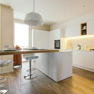 Idee per una cucina minimal con ante bianche, paraspruzzi bianco, isola, lavello sottopiano, ante lisce, elettrodomestici da incasso, pavimento in legno massello medio, pavimento marrone e top bianco