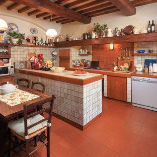 フィレンツェの地中海スタイルのおしゃれなキッチン (ダブルシンク、白いキャビネット、タイルカウンター、白いキッチンパネル、白い調理設備、テラコッタタイルの床、赤い床、白いキッチンカウンター、表し梁) の写真