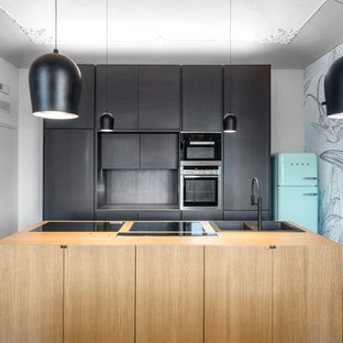 Zweizeilige Moderne Wohnküche mit Einbauwaschbecken, flächenbündigen Schrankfronten, schwarzen Schränken, Arbeitsplatte aus Holz, Küchenrückwand in Schwarz, bunten Elektrogeräten, Zementfliesen, Kücheninsel und buntem Boden