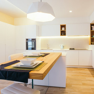 This is an example of a large contemporary u-shaped eat-in kitchen in Bologna with flat-panel cabinets, white cabinets, white splashback, medium hardwood floors, an island, brown floor and black appliances.