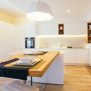 Foto di una grande cucina design con ante lisce, ante bianche, paraspruzzi bianco, pavimento in legno massello medio, isola, pavimento marrone e elettrodomestici neri