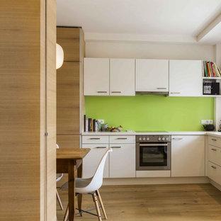 Esempio di una cucina minimalista con ante bianche, paraspruzzi verde, pavimento in legno massello medio, nessuna isola, top bianco, lavello da incasso, ante lisce e pavimento beige