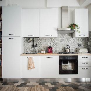 Diseño de cocina comedor lineal, actual, pequeña, sin isla, con salpicadero de azulejos de porcelana, electrodomésticos de acero inoxidable y suelo de baldosas de porcelana