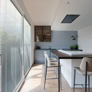 Ispirazione per una cucina contemporanea di medie dimensioni con lavello sottopiano, ante lisce, ante blu, top in legno, elettrodomestici da incasso, pavimento in legno massello medio, pavimento marrone e top marrone