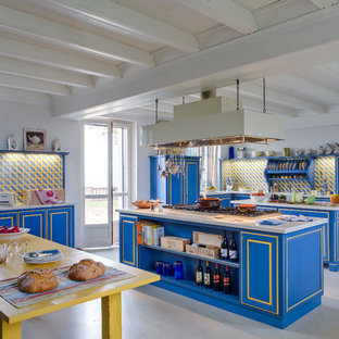 Ispirazione per un'ampia cucina industriale con ante con riquadro incassato, ante blu, paraspruzzi giallo, 2 o più isole e paraspruzzi con piastrelle in ceramica