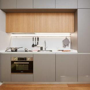 Пример оригинального дизайна: маленькая линейная кухня в стиле модернизм с врезной раковиной, плоскими фасадами, серыми фасадами, белым фартуком, техникой из нержавеющей стали, паркетным полом среднего тона, белой столешницей и коричневым полом без острова