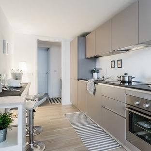 Immagine di una cucina design di medie dimensioni con ante lisce, ante grigie, paraspruzzi bianco, elettrodomestici in acciaio inossidabile, pavimento in gres porcellanato, nessuna isola e pavimento marrone