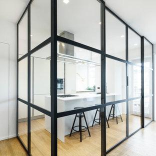 На фото: отдельная, параллельная кухня среднего размера в современном стиле с плоскими фасадами, белыми фасадами, островом, белым фартуком, паркетным полом среднего тона и коричневым полом