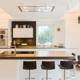 Идея дизайна: большая линейная кухня в современном стиле с плоскими фасадами, белыми фасадами, островом, врезной раковиной, столешницей из бетона и техникой из нержавеющей стали