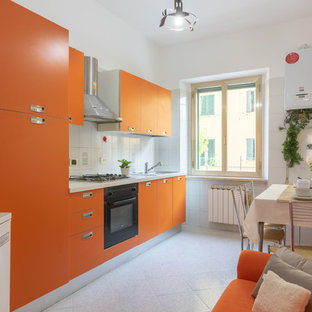 Photo of a small modern single-wall open plan kitchen in Other with a drop-in sink, flat-panel cabinets, orange cabinets, laminate benchtops, white splashback, porcelain splashback, black appliances, porcelain floors, no island, multi-coloured floor and white benchtop.