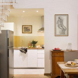 Esempio di una cucina minimal con lavello da incasso, ante lisce, ante bianche, top in legno, paraspruzzi a effetto metallico, paraspruzzi con lastra di vetro e pavimento grigio