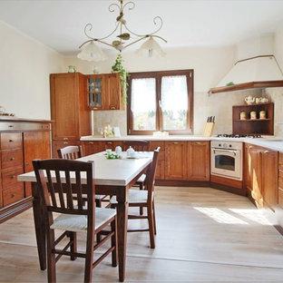 Esempio di una grande cucina country con ante in stile shaker, ante in legno bruno, paraspruzzi beige, elettrodomestici bianchi e parquet chiaro
