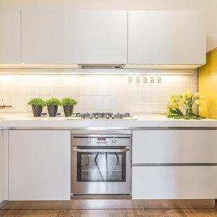 Idee per una cucina a L minimalista di medie dimensioni con ante lisce, ante bianche, top in superficie solida, paraspruzzi beige, paraspruzzi con piastrelle in ceramica, elettrodomestici in acciaio inossidabile e pavimento in legno massello medio