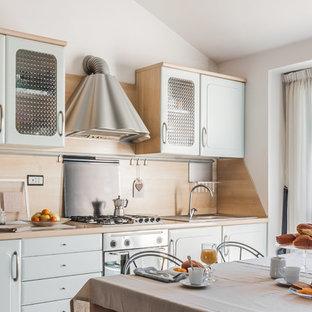 Foto di una cucina in campagna con lavello integrato, ante con riquadro incassato, ante blu, top in legno, paraspruzzi beige, paraspruzzi in legno, elettrodomestici in acciaio inossidabile e nessuna isola