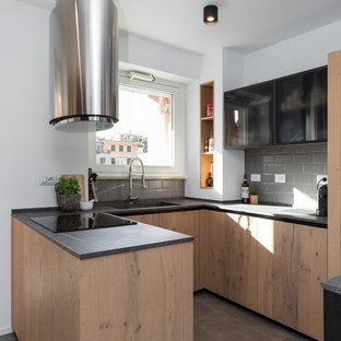 Immagine di una cucina ad U minimal con lavello integrato, ante lisce, ante in legno scuro, paraspruzzi grigio, paraspruzzi con piastrelle diamantate, penisola, pavimento grigio e top nero