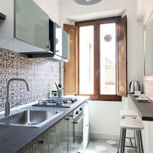 Foto di una piccola cucina mediterranea con lavello da incasso, ante lisce, ante verdi, paraspruzzi multicolore, elettrodomestici in acciaio inossidabile, pavimento multicolore e top nero