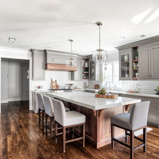 Traditional open concept kitchen ideas - Elegant u-shaped dark wood floor and brown floor open concept kitchen photo in Other with a farmhouse sink, shaker cabinets, medium tone wood cabinets, concrete countertops, white backsplash, subway tile backsplash, black appliances, an island and gray countertops