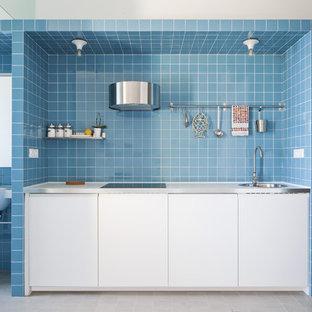 Idee per una piccola cucina lineare costiera con ante lisce, ante bianche, paraspruzzi blu, paraspruzzi con piastrelle in ceramica, elettrodomestici da incasso, nessuna isola, pavimento bianco e lavello a vasca singola