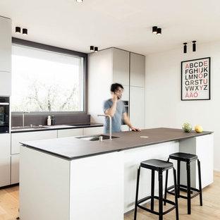 Idee per una cucina moderna di medie dimensioni con lavello sottopiano, top in marmo, parquet chiaro, isola, top nero, ante lisce, ante grigie, paraspruzzi a finestra e pavimento beige