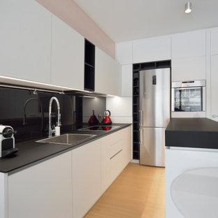Ispirazione per una cucina design con ante lisce, ante bianche, isola, lavello a vasca singola, paraspruzzi nero, elettrodomestici in acciaio inossidabile, parquet chiaro, pavimento beige e top nero