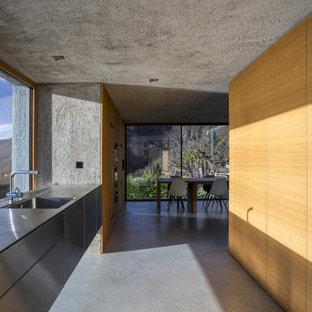 Foto di una cucina parallela minimalista con lavello integrato, ante lisce, ante in legno scuro, pavimento in cemento, nessuna isola, pavimento grigio e top grigio
