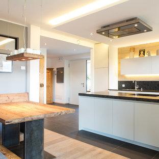 Foto di una grande cucina rustica con ante lisce, ante bianche, paraspruzzi nero e isola