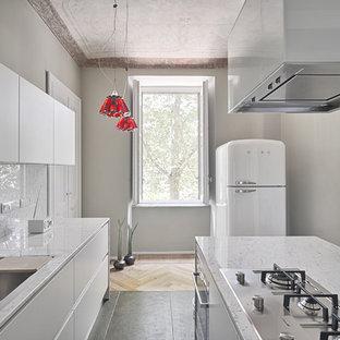 Foto di una cucina ad U mediterranea con ante bianche, isola, lavello sottopiano, top in marmo, paraspruzzi in lastra di pietra e elettrodomestici bianchi