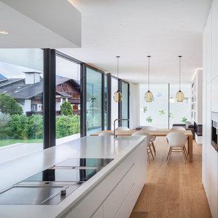 Inredning av ett modernt vit vitt kök, med en integrerad diskho, släta luckor, vita skåp, integrerade vitvaror, mellanmörkt trägolv, en köksö och beiget golv