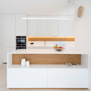 Medium sized contemporary u-shaped open plan kitchen in Venice with an island, flat-panel cabinets, white cabinets, white splashback, white appliances and beige floors.