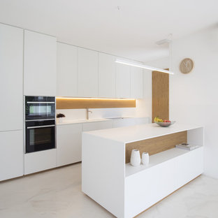 Medium sized contemporary single-wall open plan kitchen in Venice with flat-panel cabinets, white cabinets, black appliances, a breakfast bar and white floors.