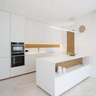 Ispirazione per una cucina design di medie dimensioni con ante lisce, ante bianche, elettrodomestici neri, una penisola e pavimento bianco