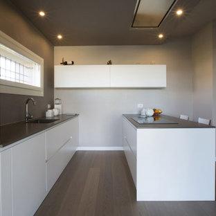 Esempio di una cucina parallela contemporanea di medie dimensioni con lavello integrato, ante lisce, ante bianche, penisola, pavimento marrone e top grigio