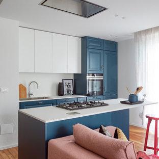 Immagine di una cucina contemporanea di medie dimensioni con lavello da incasso, ante lisce, ante blu, elettrodomestici in acciaio inossidabile, pavimento in legno massello medio, isola, pavimento marrone e top bianco