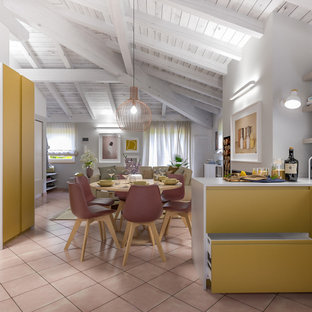 Design ideas for a mid-sized contemporary u-shaped open plan kitchen in Milan with a double-bowl sink, flat-panel cabinets, yellow cabinets, solid surface benchtops, grey splashback, glass sheet splashback, stainless steel appliances, terra-cotta floors, with island, pink floor and grey benchtop.