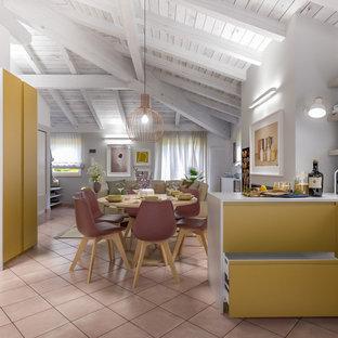 ミラノの中くらいのコンテンポラリースタイルのおしゃれなキッチン (ダブルシンク、フラットパネル扉のキャビネット、黄色いキャビネット、人工大理石カウンター、グレーのキッチンパネル、ガラス板のキッチンパネル、シルバーの調理設備、テラコッタタイルの床、ピンクの床、グレーのキッチンカウンター) の写真