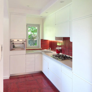 Contemporary kitchen designs - Example of a trendy l-shaped red floor kitchen design in Rome with a double-bowl sink, flat-panel cabinets, white cabinets, red backsplash, stainless steel appliances, no island and gray countertops