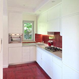 Foto di una cucina a L contemporanea con lavello a doppia vasca, ante lisce, ante bianche, paraspruzzi rosso, elettrodomestici in acciaio inossidabile, nessuna isola, top grigio e pavimento rosso