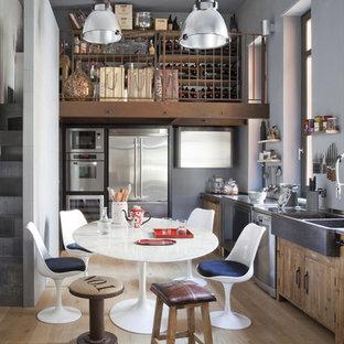 Cette image montre une cuisine américaine bohème en L avec un évier de ferme, un placard à porte plane, des portes de placard en bois brun, un électroménager en acier inoxydable, un sol en bois clair, aucun îlot, un sol beige et un plan de travail gris.