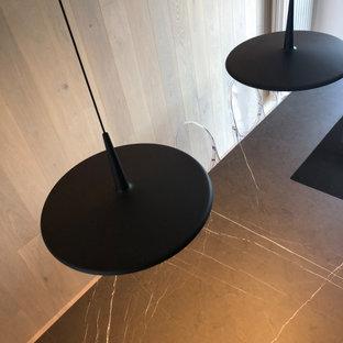 Modelo de cocina comedor lineal y bandeja, contemporánea, pequeña, con fregadero bajoencimera, armarios con paneles lisos, encimera de mármol, electrodomésticos de acero inoxidable, suelo de madera clara, una isla y encimeras negras
