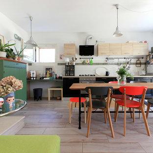 Foto di una cucina lineare eclettica con ante lisce, ante nere, elettrodomestici in acciaio inossidabile e isola