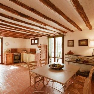 Offene, Große Mediterrane Küche in L-Form mit Waschbecken, offenen Schränken, hellen Holzschränken, Küchengeräten aus Edelstahl, Terrakottaboden und rosa Boden in Sonstige