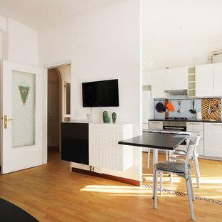 Idee per una cucina ad ambiente unico industriale con lavello da incasso, ante lisce, ante bianche, paraspruzzi multicolore, elettrodomestici in acciaio inossidabile, parquet chiaro e top nero