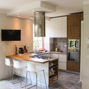Ispirazione per una cucina ad U minimal di medie dimensioni con lavello sottopiano, ante lisce, ante in legno bruno, paraspruzzi con piastrelle in ceramica, pavimento in cemento, penisola, paraspruzzi grigio, elettrodomestici in acciaio inossidabile e pavimento grigio