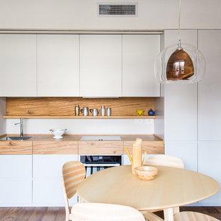 ミラノの中サイズのモダンスタイルのおしゃれなキッチン (ドロップインシンク、フラットパネル扉のキャビネット、グレーのキャビネット、木材カウンター、茶色いキッチンパネル、木材のキッチンパネル、無垢フローリング、アイランドなし、茶色い床) の写真