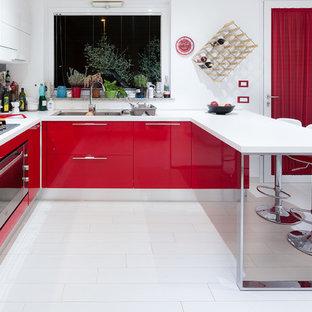 Immagine di una cucina ad U design con lavello a doppia vasca, ante lisce, ante rosse, paraspruzzi grigio, elettrodomestici in acciaio inossidabile e penisola