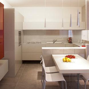 Inredning av ett modernt stort kök, med en nedsänkt diskho, släta luckor, vita skåp, bänkskiva i glas, vitt stänkskydd, glaspanel som stänkskydd och rostfria vitvaror