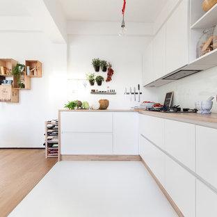 Idee per una grande cucina minimal con lavello da incasso, ante lisce, ante bianche, top in legno, paraspruzzi bianco, pavimento in gres porcellanato e paraspruzzi con lastra di vetro