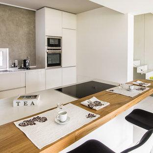 Foto di una grande cucina minimal con lavello da incasso, ante lisce, ante bianche, paraspruzzi grigio, elettrodomestici in acciaio inossidabile e penisola