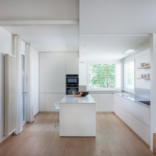 Esempio di una cucina minimalista chiusa e di medie dimensioni con paraspruzzi grigio, parquet chiaro, top grigio, ante lisce, ante bianche, elettrodomestici da incasso e pavimento beige